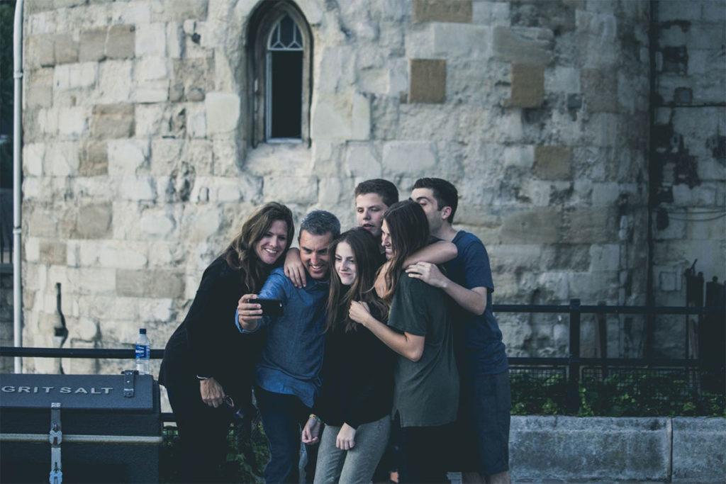 Auf diesem Bild sieht man einen Mann der ein Selfie mit seiner Familie macht. Seine Familie hilft ihm seinen Liebeskummer überwinden zu können.