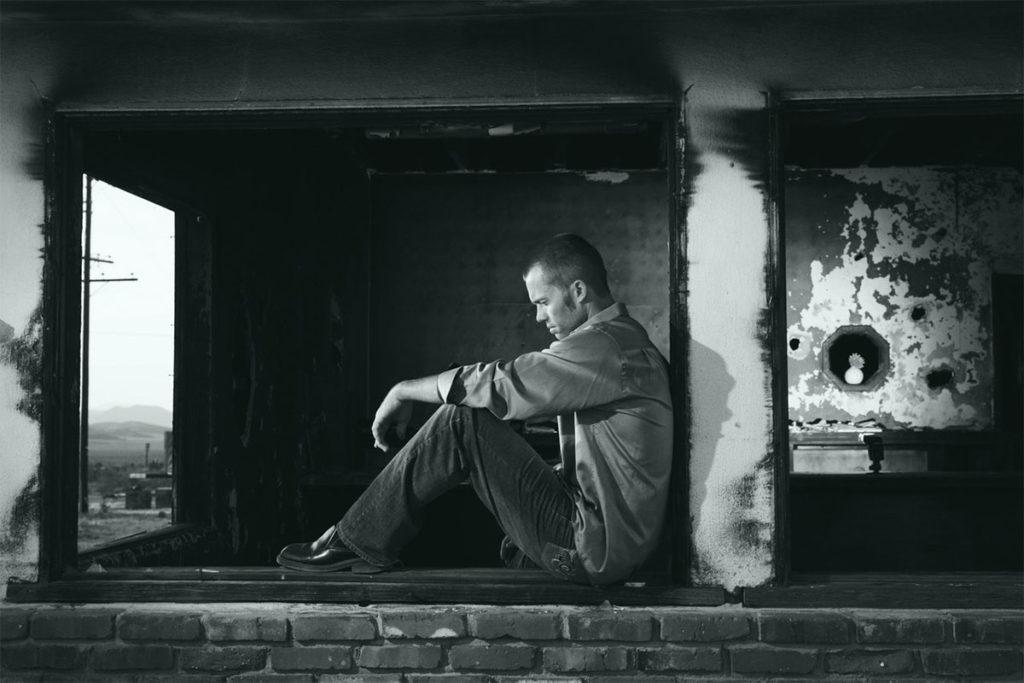 Auf diesem Bild sieht man einen Mann der auf einer Mauer sitzt und seinen Liebeskummer überwinden muss. Er sieht sehr traurig aus.