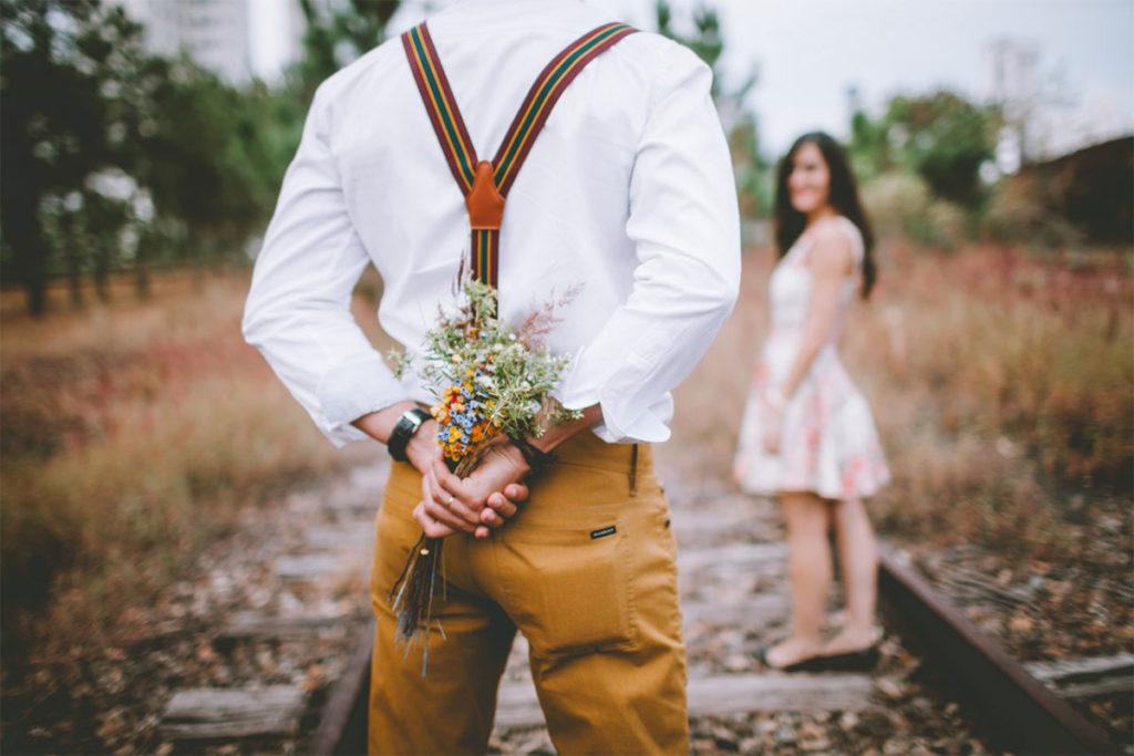 Auf diesem Bild sieht man keinen attraktiven Mann sondern einen Mann der sehr needy ist. Er bringt einer Frau einen Blumenstrauß zum Date mit um sie zu beeindrucken.