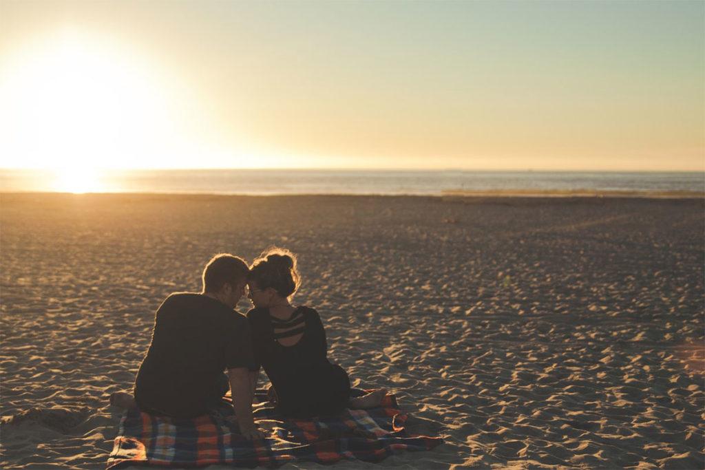 Auf diesem Bild sieht man einen Mann der eine Freundin finden wollte und jetzt mit seiner Freundin am Strand sitzt um den Sonnenuntergang anzusehen