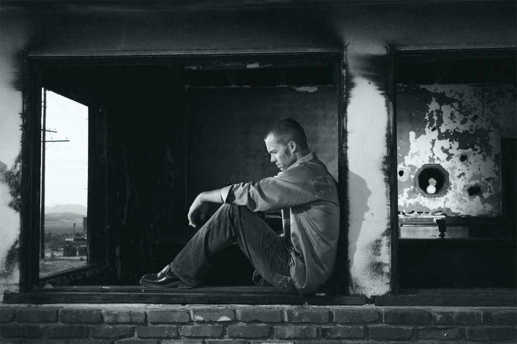 Der Mann auf diesem Bild sitzt und einer Mauer und ist traurig, weil er sich getrennt hat und eine neue Freundin finden muss