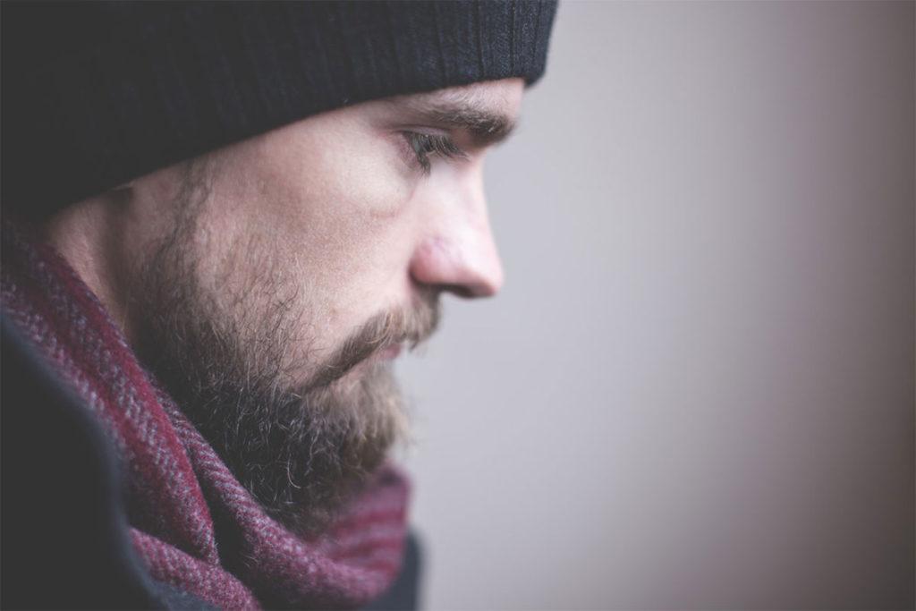 Auf diesem Bild sieht man einen Mann mit Mütze der sehr traurig ist weil er gefriendzoned wurde.