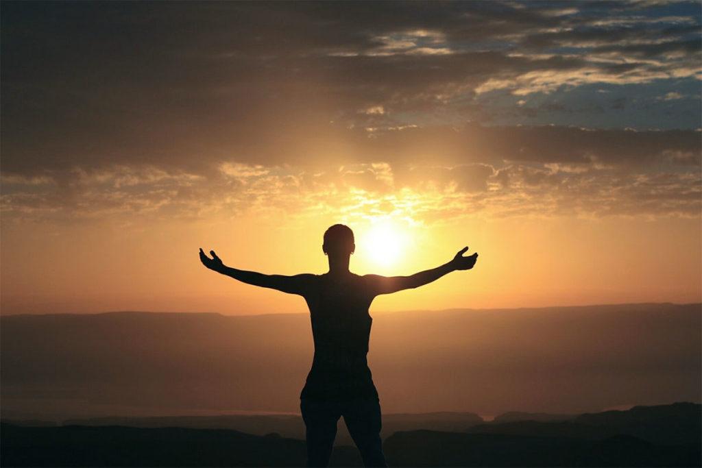Auf diesem Bild steht ein Mann auf einem Berg und schaut sich den Sonnenuntergang an. Er streckt seine Arme aus, weil er selbstbewusst werden möchte.