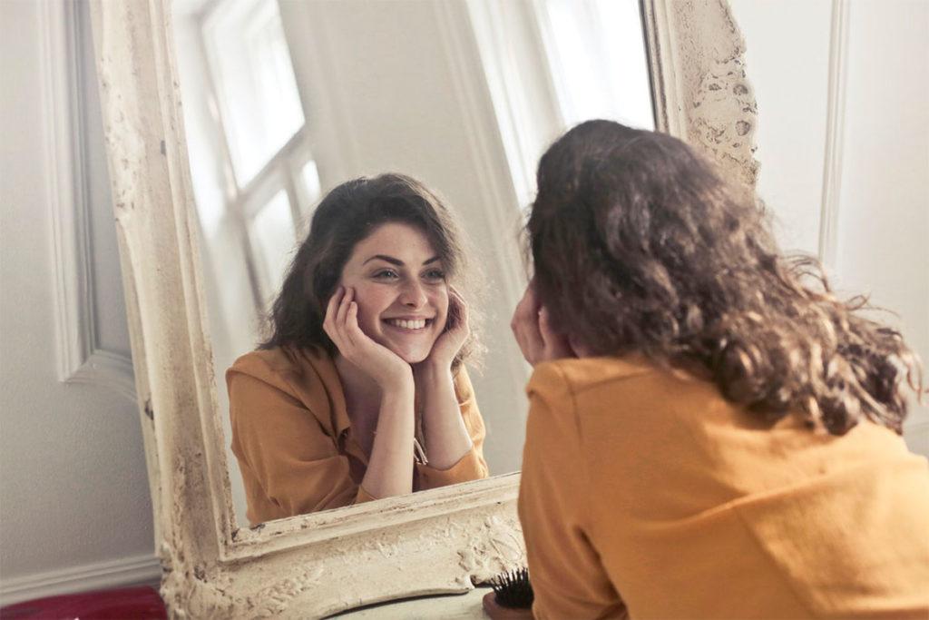 Das Mädchen auf diesem Bild lächelt in den Spiegel weil sie selbstbewusst werden gelernt hat indem sie sich selbst akzeptiert.
