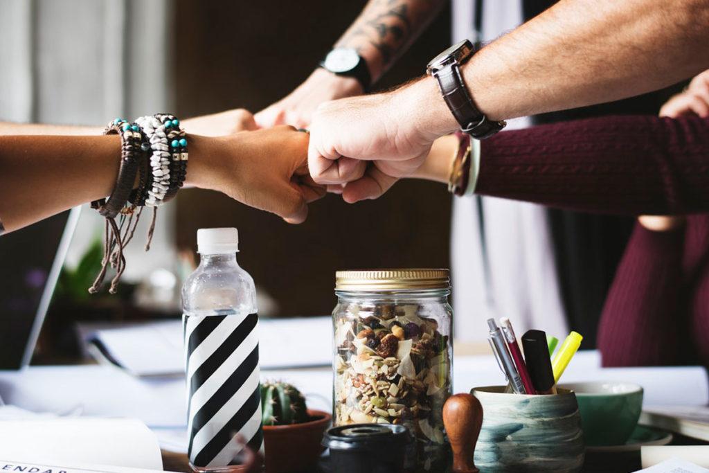 Auf diesem Bild sieht man 5 Leute die ihre Fäuste zusammenhalten. Sie sind ein Team und wollen gemeinsam selbstbewusst werden.