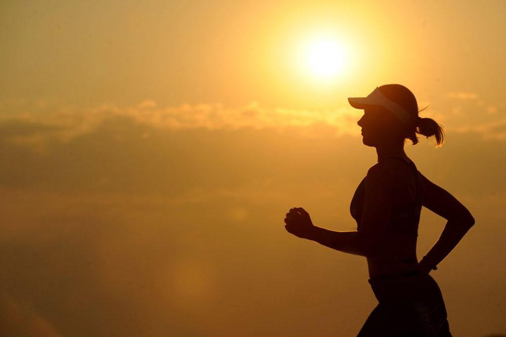 Die Frau auf diesem Bild läuft früh morgens beim Sonnenaufgang um selbstbewusst werden zu können.