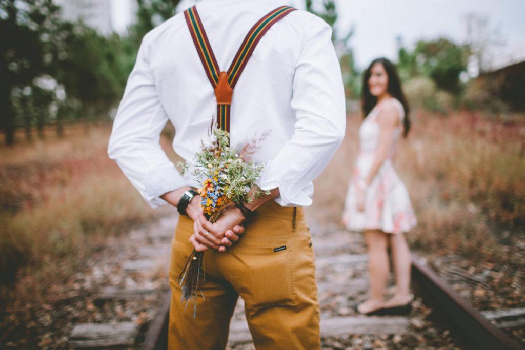 Auf diesem Bild sieht man einen Mann und eine Frau die sich für ein zweites Date verabredet haben. Der Mann hält hinter seinem Rücken einen Blumenstrauß.