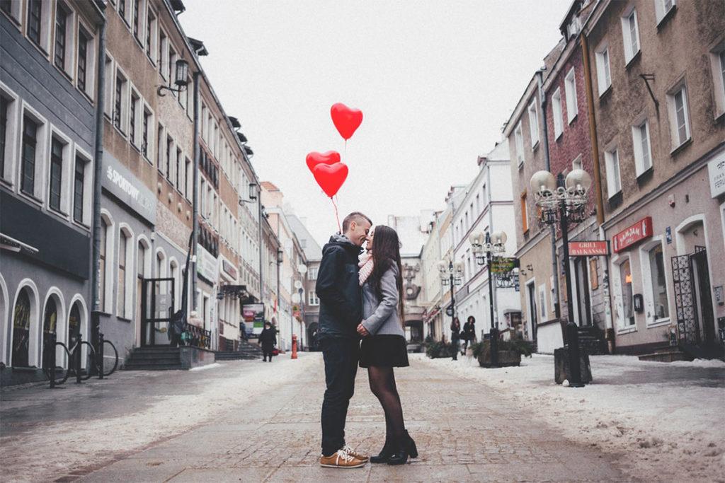 Auf diesem Bild sieht man einen Jungen und ein Mädchen auf der Straße stehen die ihr zweites Date haben und sich küssen.