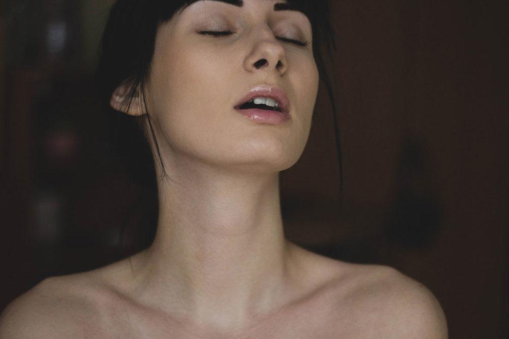 Auf diesem Bild sieht man das Gesicht einer Frau. Sie scheint gerade Sex zu haben.