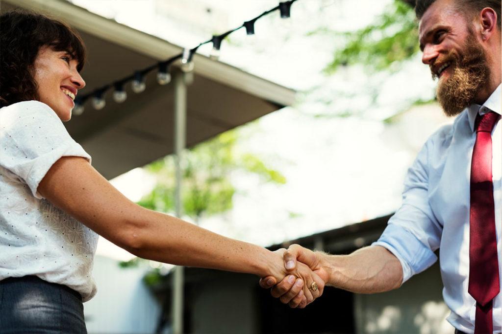 Der Mann auf diesem Bild hat Frauen ansprechen gelernt und stellt sich gerade einer Frau vor, während er ihre Hand schüttelt.