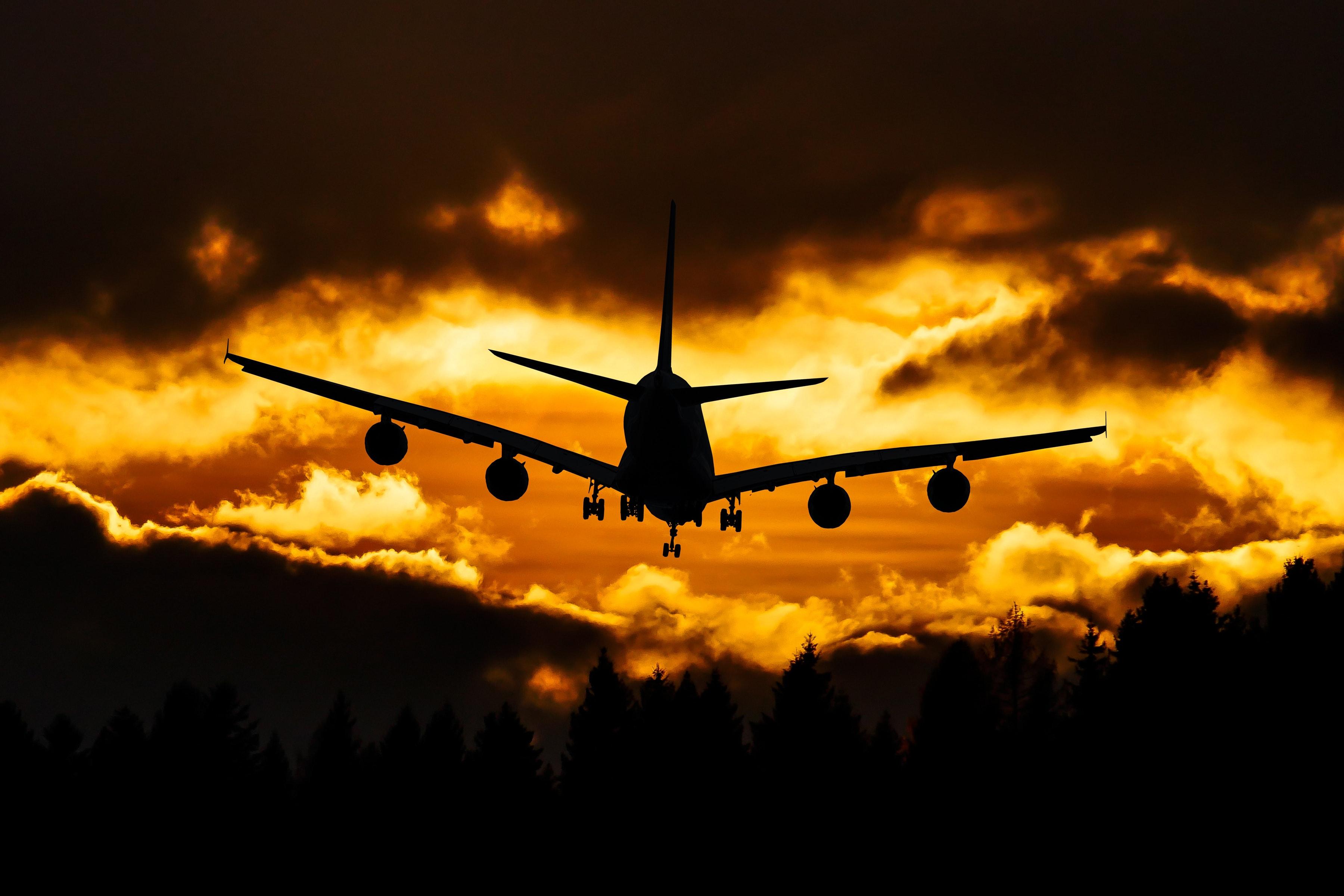 Männlicher Werden - Flugzeug fliegt Sonnenuntergang entgegen