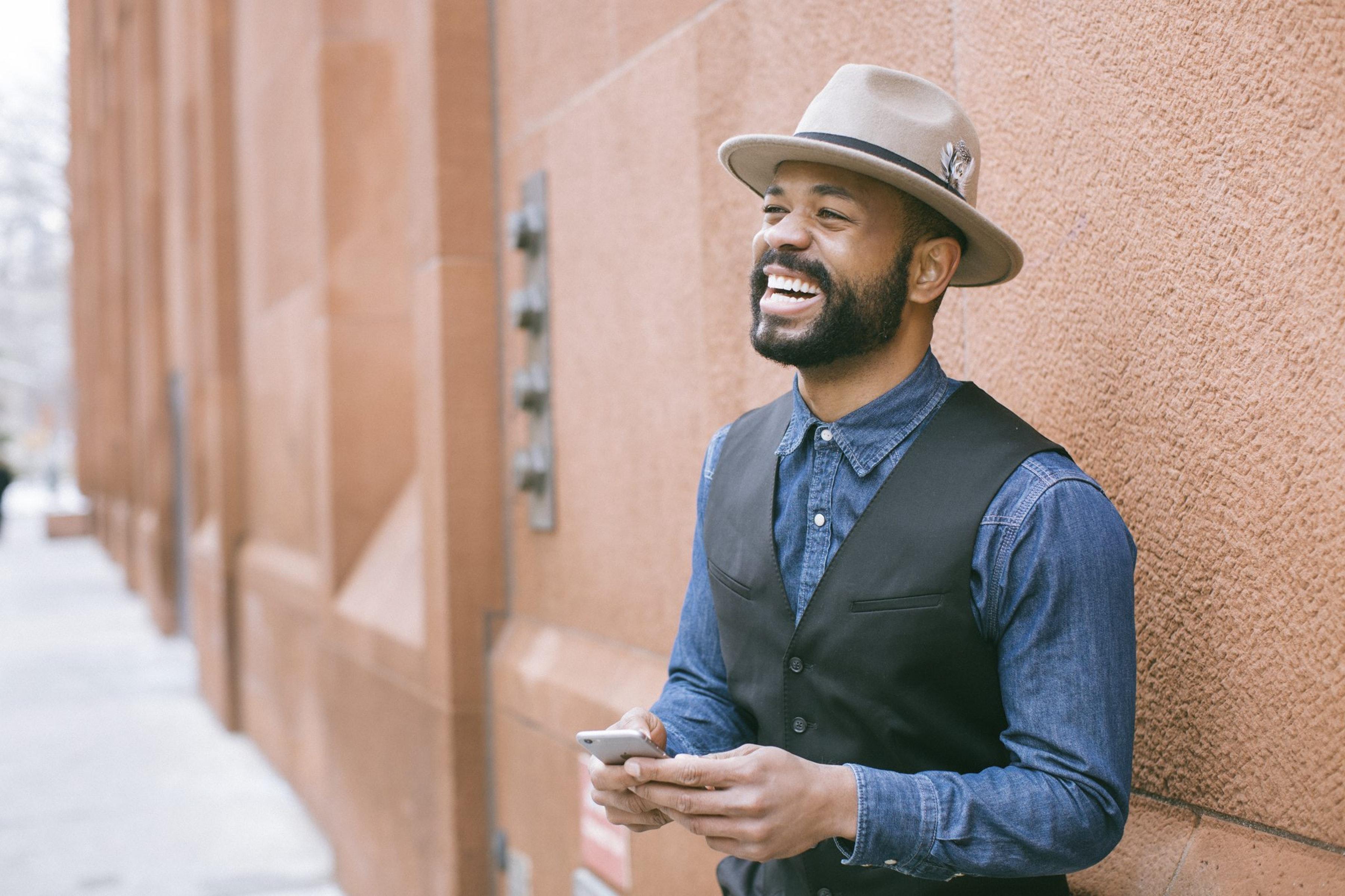 attraktiver werden Mann mit modischen Hut lacht